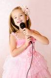 Menina bonita com o microfone no vestido da princesa Fotos de Stock