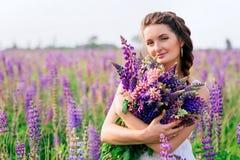 A menina bonita com o ramalhete do lupine floresce nas mãos Fotos de Stock Royalty Free