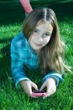Menina bonita com o telefone de pilha que coloca na grama Fotografia de Stock