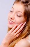 A menina bonita com olhos fechados toca em sua cara Imagem de Stock Royalty Free