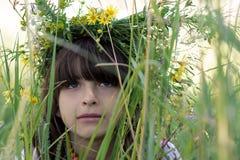 A menina bonita com olhos verdes e um garlang colorido feito de flores selvagens em sua cabeça senta-se na grama verde alta em um Imagens de Stock Royalty Free