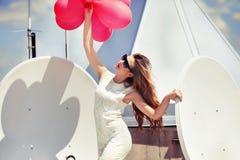 Menina bonita com os balões no telhado Foto de Stock