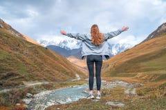 A menina bonita com os braços aumentados às montanhas de Svaneti, montanha Shkhara, relaxa ao viajar imagem de stock royalty free