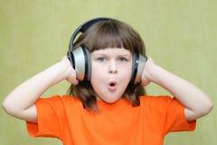 A menina bonita com os fones de ouvido em sua cabeça dobrou o bordo do tubo Fotografia de Stock Royalty Free