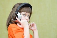 A menina bonita com os fones de ouvido em sua cabeça escuta atentamente t Foto de Stock Royalty Free