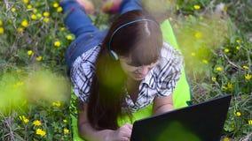 Menina bonita com os fones de ouvido que correm no parque no portátil, menina que fala no Internet no computador no parque da mol video estoque