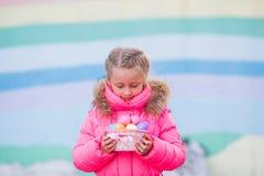 Menina bonita com os ovos coloridos na cesta para a Páscoa que anda abaixo da rua Imagens de Stock