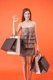 A menina bonita com pacotes está expressando Fotografia de Stock Royalty Free