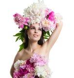 Menina bonita com peônias das flores Retrato de uma jovem mulher com flores em seu cabelo e em um vestido das flores Imagens de Stock Royalty Free
