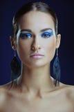 Menina bonita com pele perfeita na composição brilhante azul em brincos longos fotos de stock