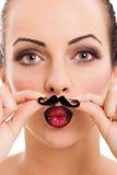 Menina bonita com a pele perfeita que guarda o bigode falsificado Fotografia de Stock