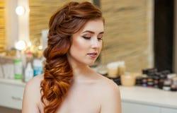 Menina bonita, com por muito tempo, peludo ruivo O cabeleireiro tece uma trança francesa, close-up em um salão de beleza imagem de stock