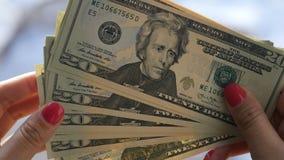 A menina bonita com pregos cor-de-rosa, posses um denominações de 20 dólares em suas mãos e conta-as, Imagens de Stock