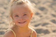 Menina bonita com Síndrome de Down na praia imagem de stock