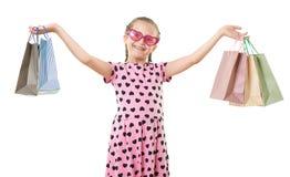 A menina bonita com saco de compras, retrato do estúdio, vestiu-se no rosa com formas do coração, fundo branco Foto de Stock Royalty Free