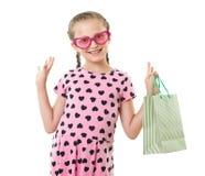 A menina bonita com saco de compras, retrato do estúdio, vestiu-se no rosa com formas do coração, fundo branco Imagens de Stock Royalty Free