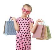 A menina bonita com saco de compras, retrato do estúdio, vestiu-se no rosa com formas do coração, fundo branco Foto de Stock
