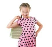 A menina bonita com saco de compras, retrato do estúdio, vestiu-se no rosa com formas do coração, fundo branco Imagens de Stock