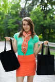 Menina bonita com sacos de compras de pano que anda na ponte de madeira Fotos de Stock