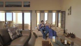 Menina bonita com seu noivo que relaxa no sofá na sala video estoque