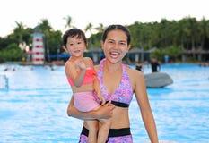 Menina bonita com sua mãe na piscina fora imagens de stock royalty free