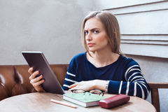 A menina bonita com a tabuleta olha suspeito Mulher que estuda e que relaxa estando em um café Fotografia de Stock Royalty Free