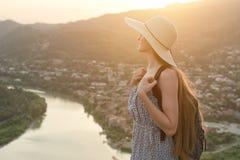 A menina bonita com trouxa e chapéu está lateralmente no fundo da cidade e do rio abaixo Imagens de Stock Royalty Free