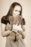Menina bonita com um brinquedo uma peluche do urso. Imagens de Stock
