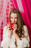 Menina bonita com um copo do chá Imagem de Stock