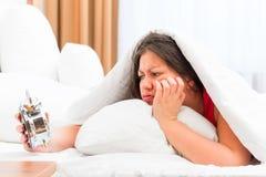 Menina bonita com um despertador nas mãos Foto de Stock