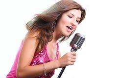 Menina bonita com um microfone que canta uma canção Fotografia de Stock Royalty Free