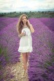 Menina bonita com um olhar pensativo em um campo da alfazema Fotografia de Stock Royalty Free