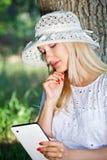 Menina bonita com um PC da tabuleta fotos de stock