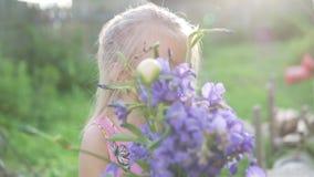 Menina bonita com um ramalhete de suportes azuis dos sinos no jardim video estoque