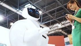 Menina bonita com um robô Tecnologias robóticos modernas O robô olha a câmera na pessoa As mostras do robô filme
