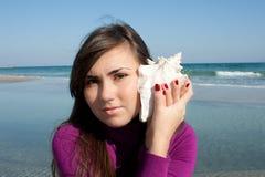 Menina bonita com um seashell Fotos de Stock Royalty Free