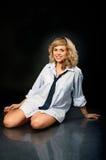 Menina bonita com um sorriso, sentando-se no assoalho Fotografia de Stock