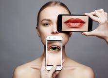 Menina bonita com um telefone na cara Redes sociais fotos de stock