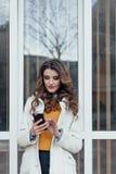 Menina bonita com um telefone na cidade imagem de stock