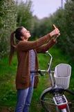 Menina bonita com uma bicicleta em um pomar de maçã Imagens de Stock