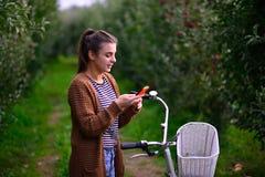 Menina bonita com uma bicicleta em um pomar de maçã Imagens de Stock Royalty Free