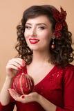 Menina bonita com uma bola vermelha do Natal Fotografia de Stock Royalty Free