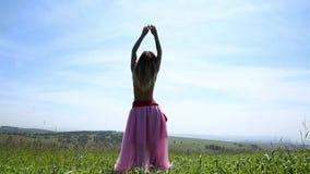 Menina bonita com uma dança despida do torso em um campo verde, vista traseira filme