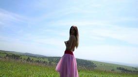 Menina bonita com uma dança despida do torso em um campo verde, vista traseira video estoque