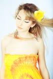 Menina bonita com uma flor em seu cabelo. imagens de stock royalty free
