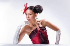 Menina bonita com uma flor vermelha e no glov branco Foto de Stock