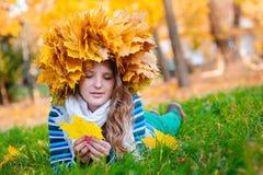 Menina bonita com uma grinalda das folhas na cabeça que encontra-se no Imagem de Stock