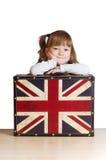 Menina bonita com uma mala de viagem com bandeira britânica imagens de stock