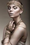 Menina bonita com uma pele de bronze, uma composição pálida e uns acessórios incomuns Imagem da beleza da arte Face da beleza fotos de stock