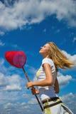 Menina bonita com uma rede da borboleta Imagem de Stock